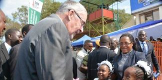 VICE PRESIDENT Dr. Guy Scott receives a bouquet of flowers on arrival at the official opening of this year's International Trade Fair in Ndola