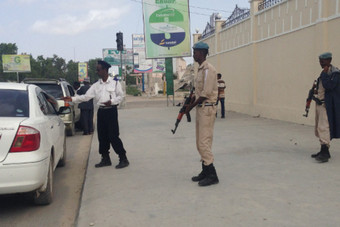 Armed Somali police on July 9, 2014, guard a traffic police officer near the Monument of the Unknown Soldier in Mogadishu. [Shukri Mohamed/Sabahi]