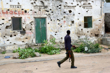 A Somali soldier passes by a damaged building as he patrols a street in Mogadishu