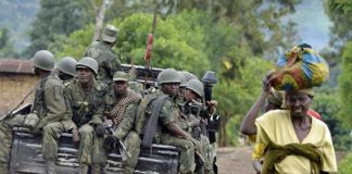 Democratic Republic of Congo soldiers sit at the back of a pick-up truck as they head towards the Mbuzi hilltop, near Rutshuru, on November 4, 2013 (AFP Photo/Junior D. Kannah)