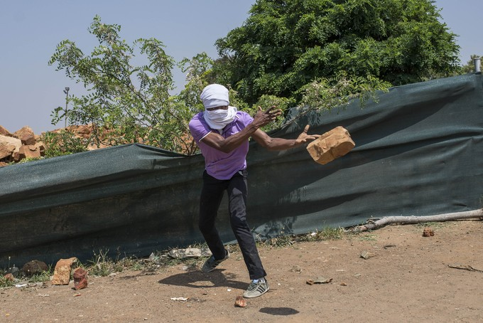 A protester uses a rock to block a road. - Image - Groundup