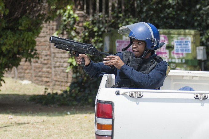 A police officer gets ready to fire a teargas cannister. - Image -  Groundup