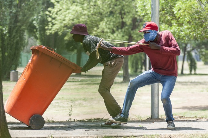 "A protester uses a ""katty"" to launch stones at the police while a colleague shields him with a bin. - Image - Groundup"