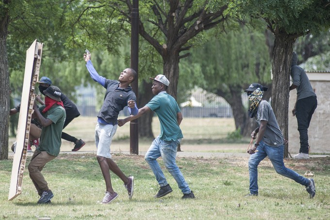 Students threw rocks at the police and protected themselves with a mattress. - Image -  Groundup
