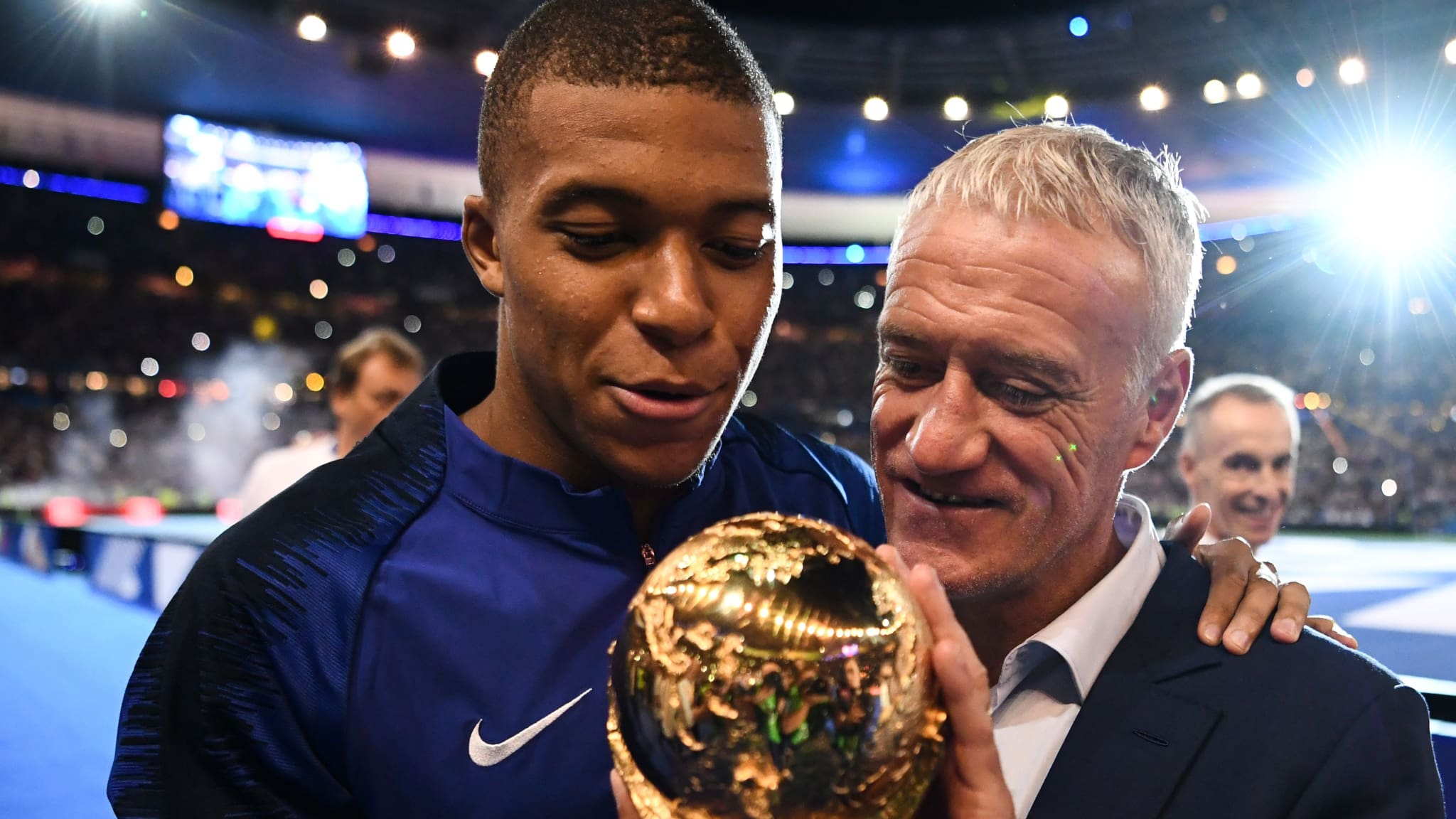 France's midfielder Kylian Mbappe (L) and France's coach Didier Deschamps pose with the 2018 World Cup trophy