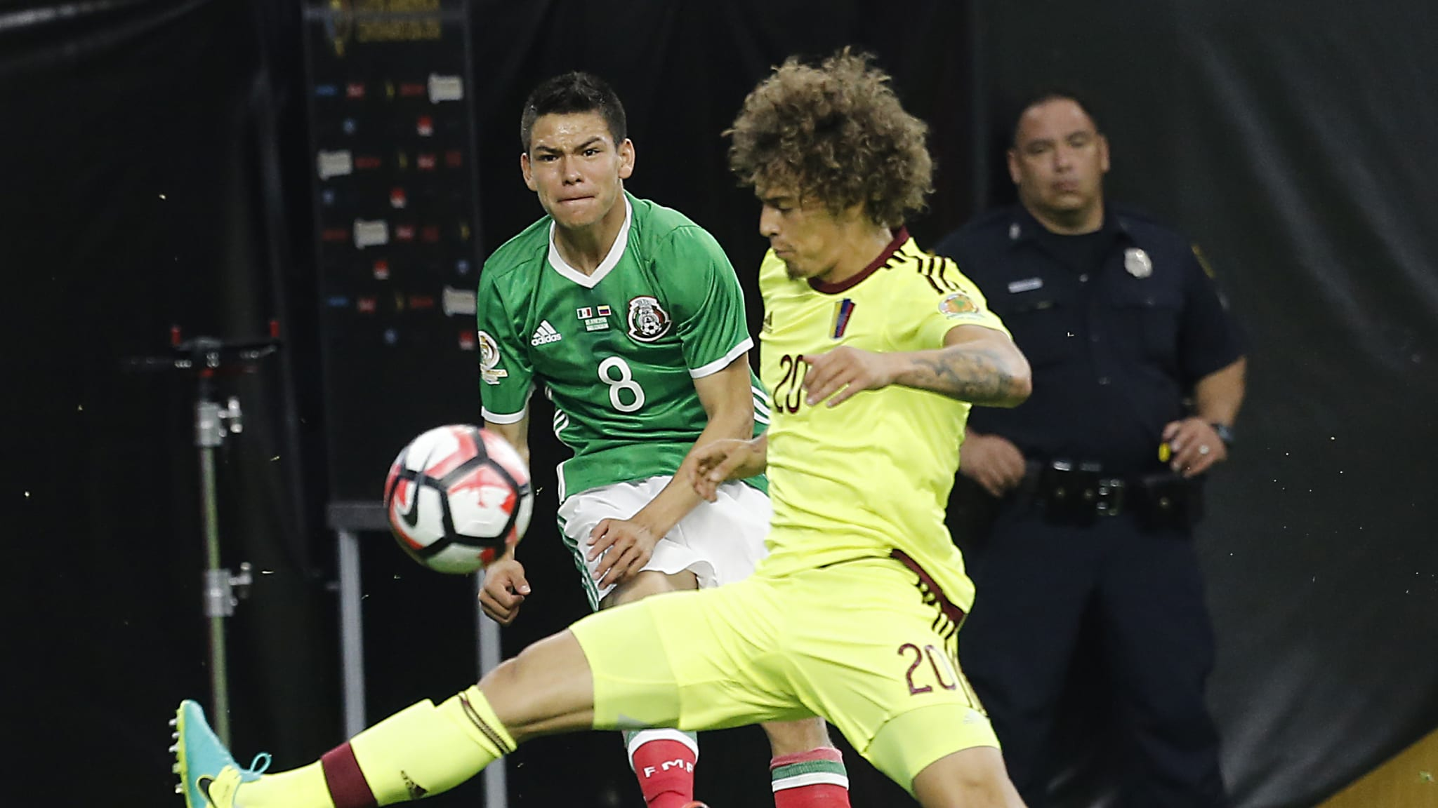Hirving Lozano of Mexico crosses the ball in front of Rolf Feltscher of Venezuela