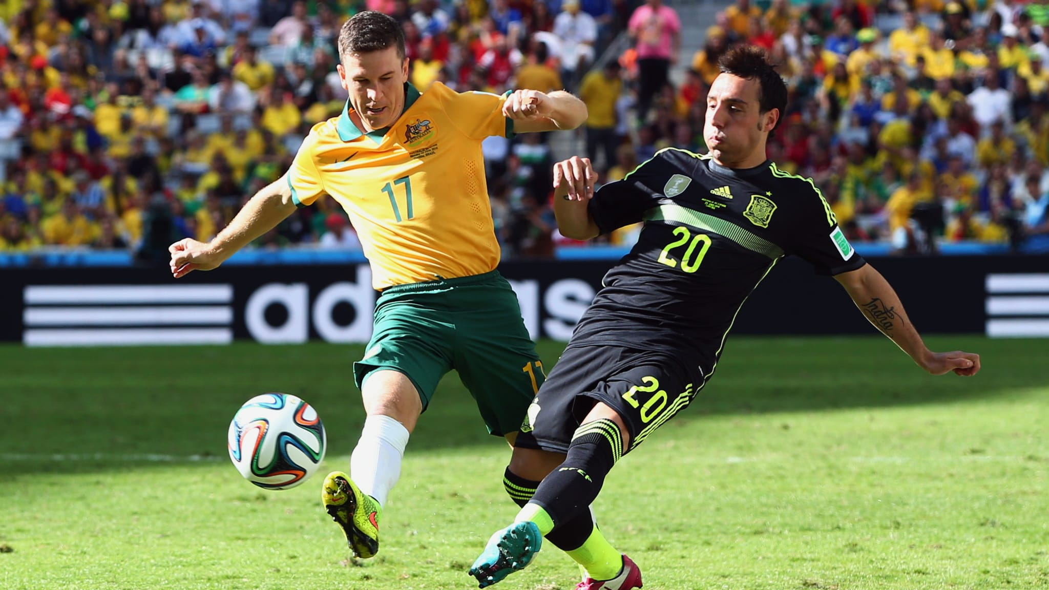 Matt McKay (L) of Australia competes with Santi Cazorla of Spain during the 2014 FIFA World Cup Brazil Group B match between Australia and Spain at Arena da Baixada on June 23, 2014 in Curitiba, Brazil.