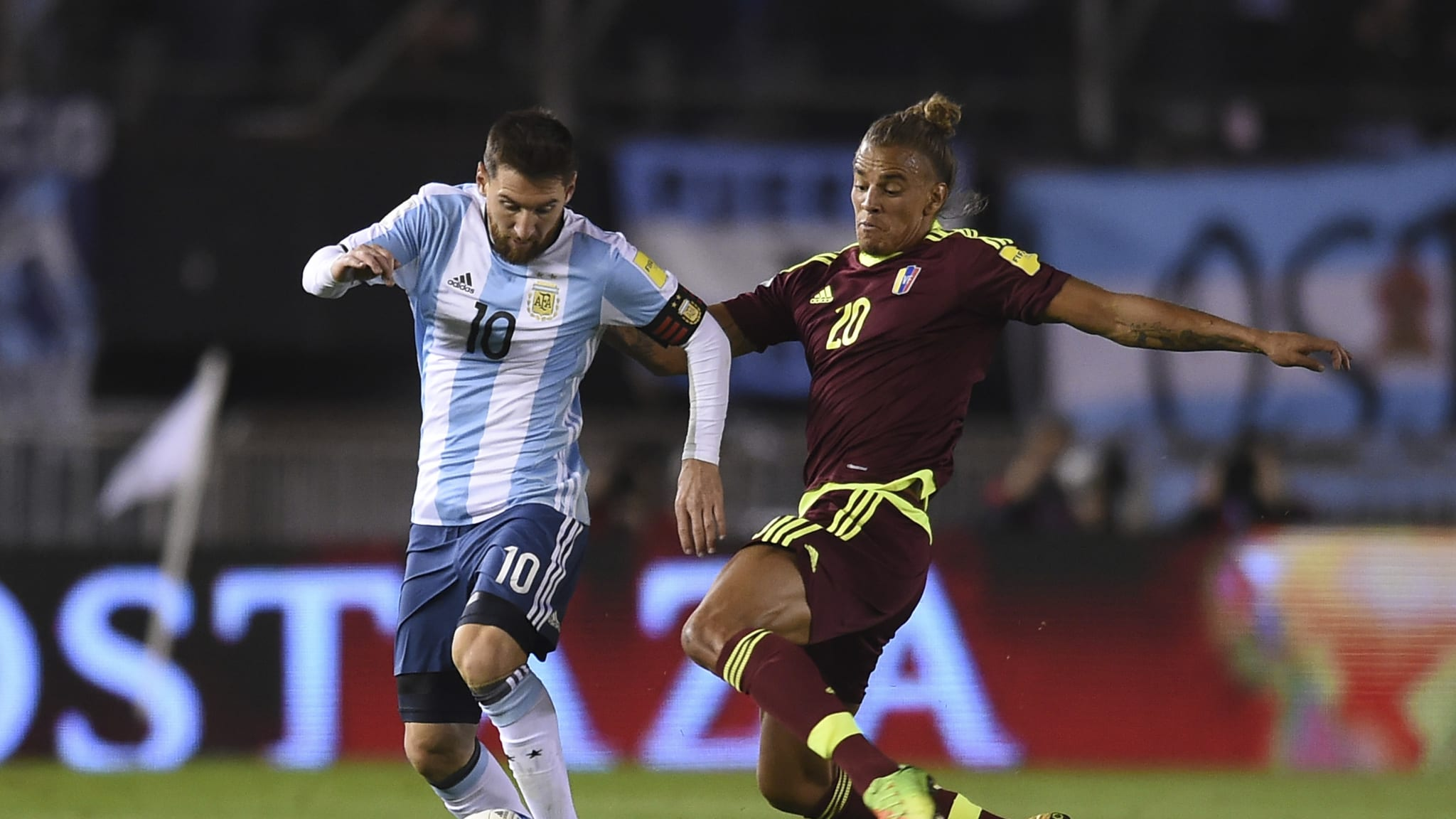 Lionel Messi of Argentina fights for ball with Rolf Feltscher of Venezuela