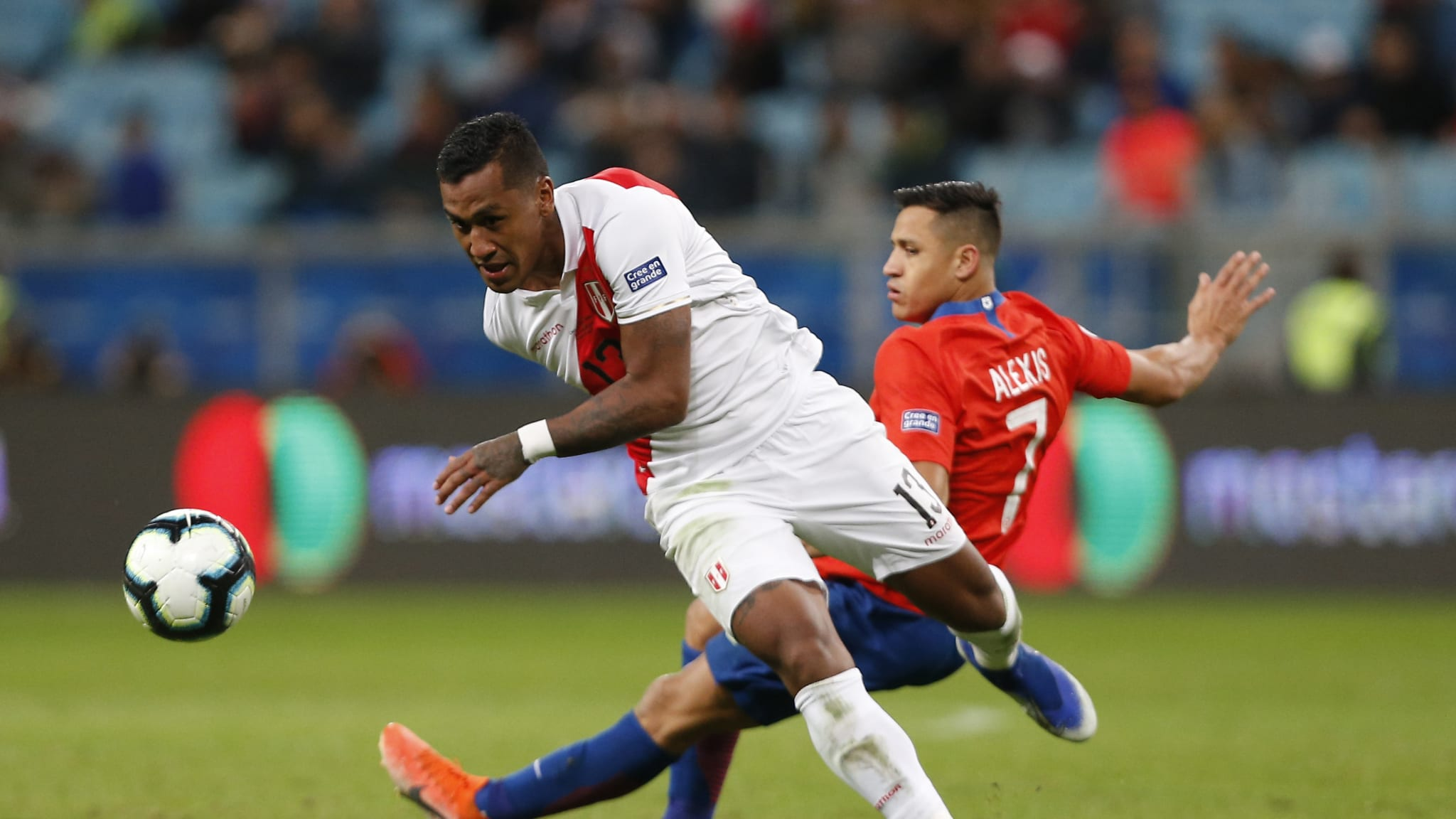 Renato Tapia of Peru fights for the ball with Alexis Sanchez of Chile