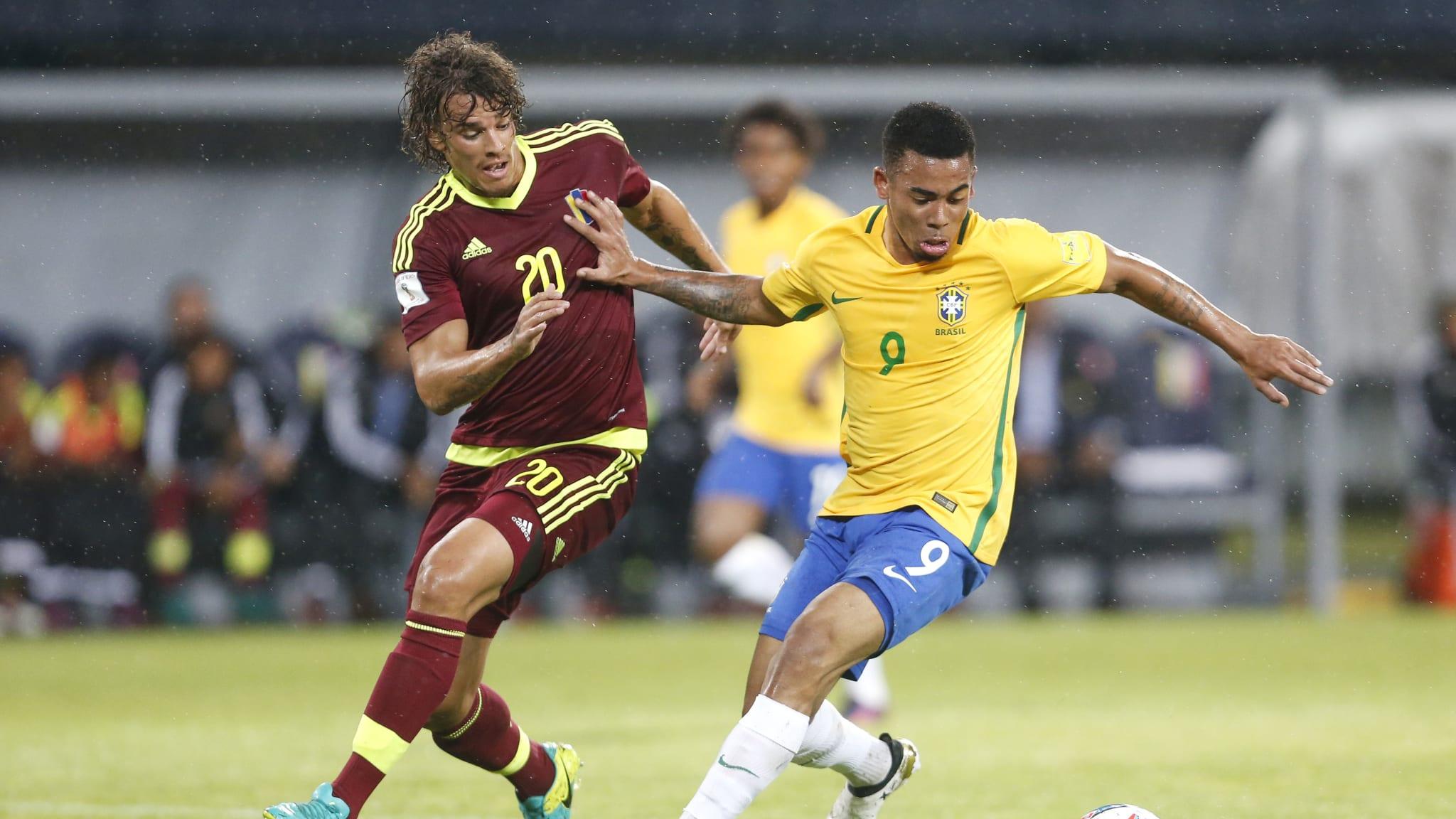 Gabriel Jesus of Brazil fights for the ball with Rolf Feltscher of Venezuela