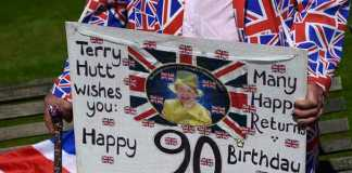 Royal fan Terry Hutt holds a placard as he stands outside of Windsor Castle in Windsor Britain April 20, 2016. Britain's Queen Elizabeth celebrates her 90th birthday in Windsor on April 21. REUTERS/Toby Melville