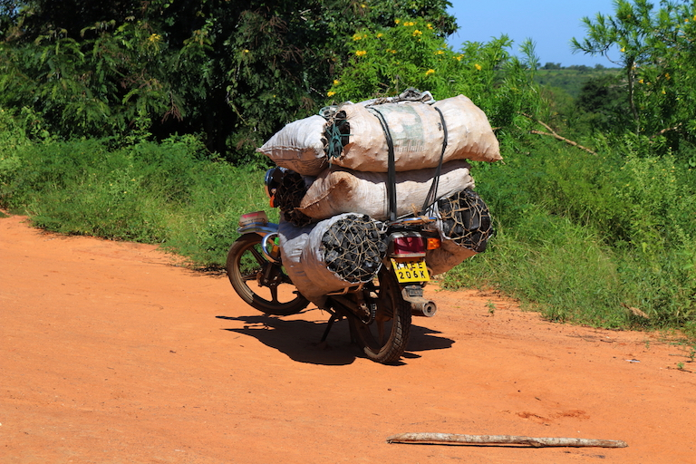 A motorcycle parked at a shopping center not far from Kaya Kauma carries a load of charcoal, a major threat to the kaya's forest. Image by Sophie Mbugua for Mongabay.