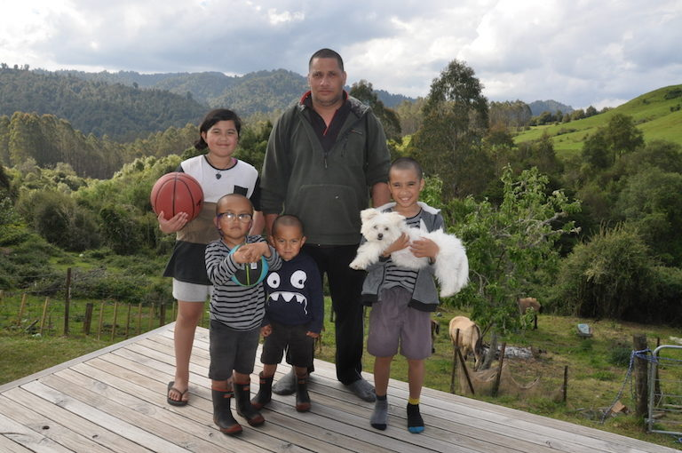 Jim Tahi, Manawa Honey's production manager, stands on his deck with one of his children and three grandchildren. Image by Monica Evans for Mongabay.