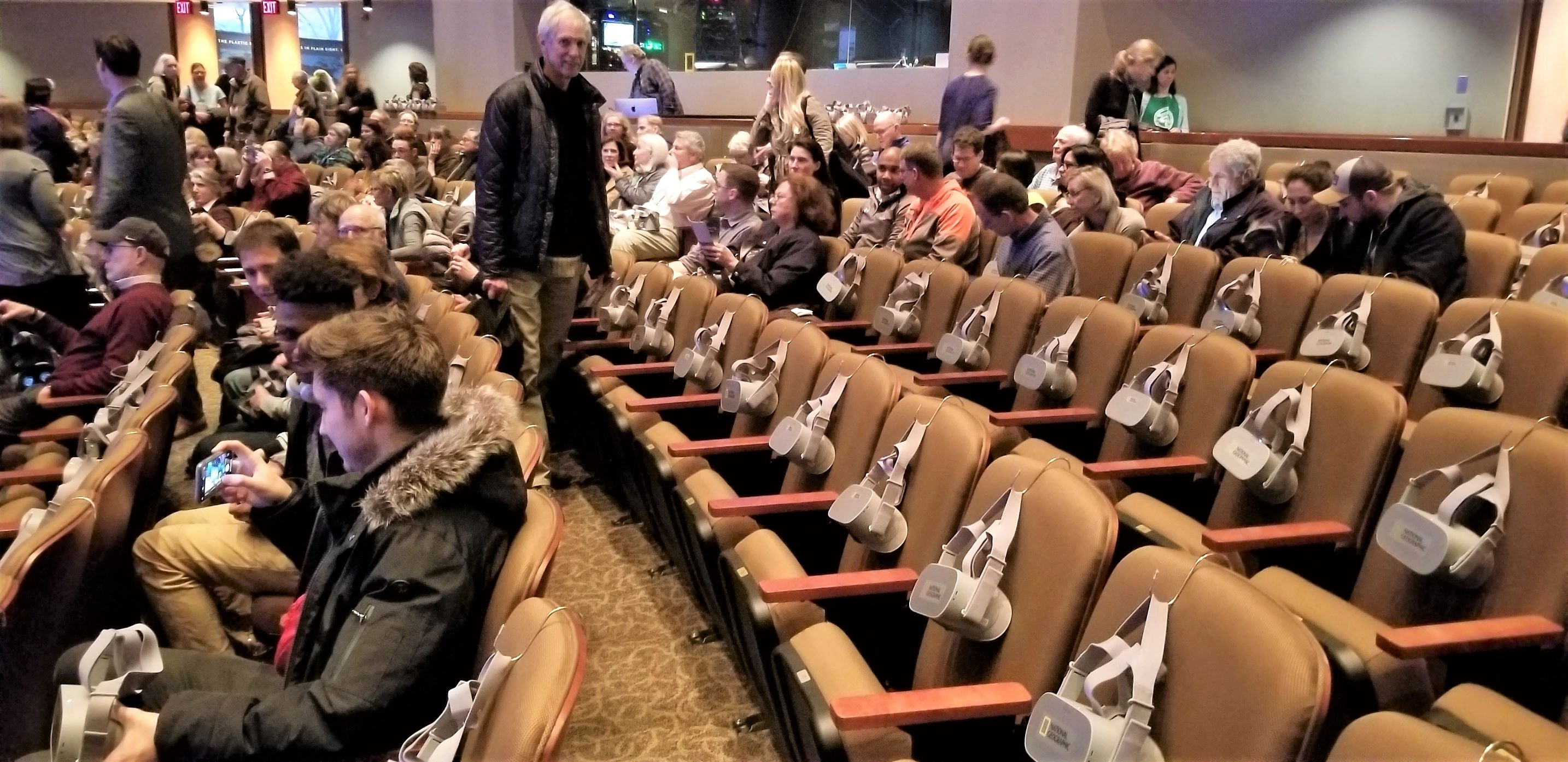 The VR-equipped auditorium at National Geographic. The use by a well-financed NGO of standard $200 Oculus Go goggles hooked onto the backs of the chairs demonstrates that groups with smaller budgets can also use VR-360 technology for their outreach efforts.