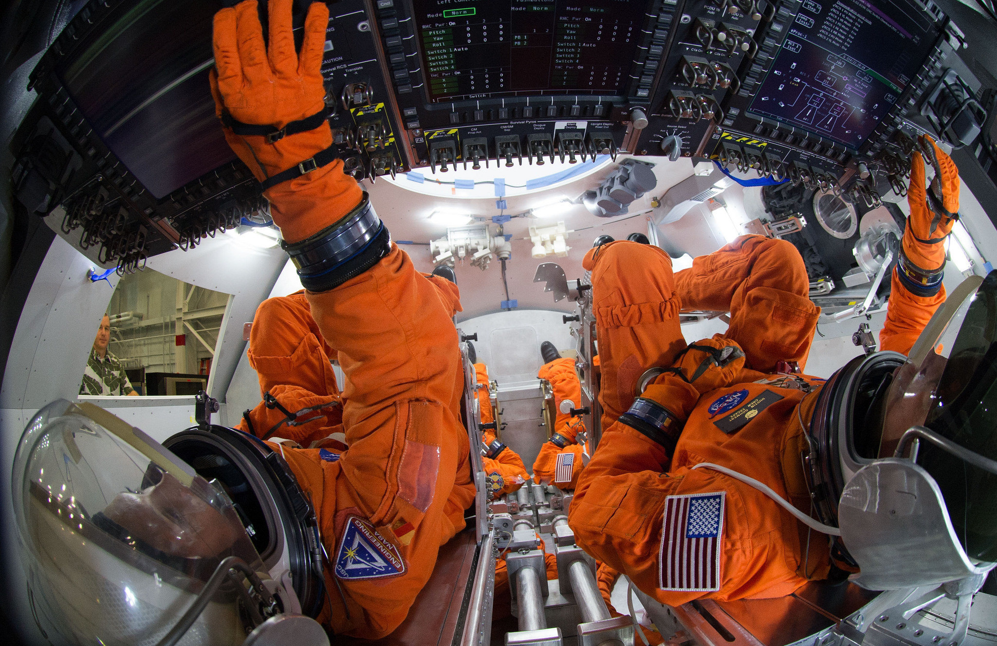 Spacesuit engineers demonstrate how four crew members would be arranged for launch inside the Orion spacecraft, using a mockup of the vehicle at Johnson Space Center. Astronauts will board Orion for a first crewed flight in 2021, and NASA hopes send humans to Mars in Orion in the 2030s