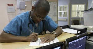 Male nurse filling out patient chart in emergency room --- Image by © Ocean/Corbis